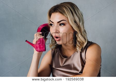 Beautiful girl holds a pink shoe in her hand and smiles
