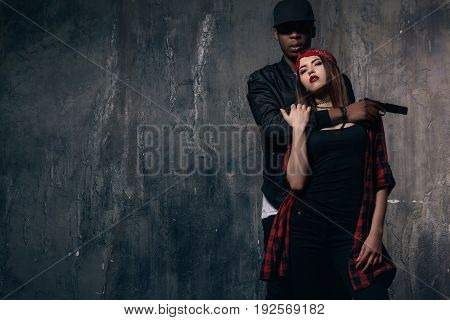 Captive girl inlove in gangster with gun. Hostage hugs with black criminal mafia person on dark background