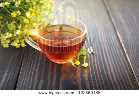 Cup of chamomile tea and a bunch of chamomile flowers on the table. Beautiful still life with herbal tea.