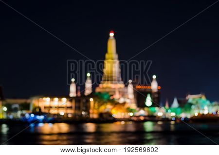 Blur bokeh background of temple in the city at night time close to big river