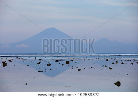 Views of the Agung volcano with reflection in the water off the island of Gili Trawangan in the early morning at low tide with exposed rocks, Indonesia