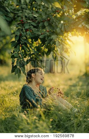in the summer the cherry garden in the sunshine cute little girl