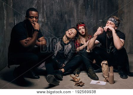 Disadvantaged group of people smokes with alcohol. Homeless gung members gets drunk. Youth addiction , social problem concept