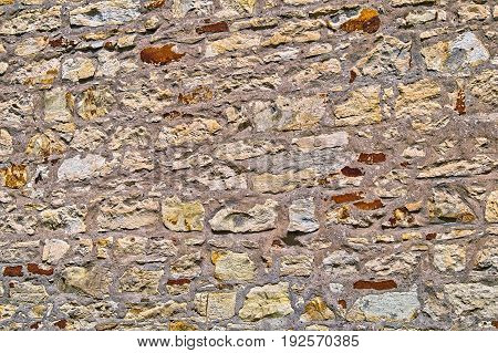 The Wall Built Of Irregular Stones Background. Texture Of Old Stonework. Space For Text. The Concept