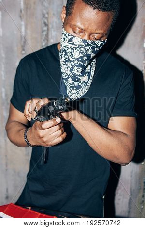 Black mercenary checks his weapon. Gangster man with gun in hand on dark gray background. Outlaw, ghetto, murderer, armed attack concept