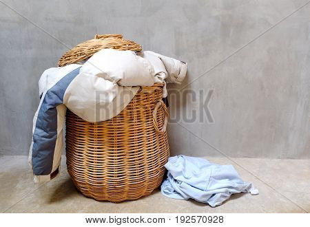 Overflowing wicker laundry basket. Household chore concept.