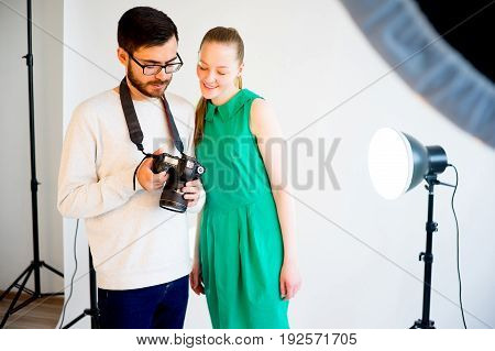 Female model working at studio with photographer