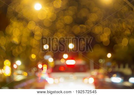 Abstract circular bokeh blurry yellow light on the road with blur white car at night