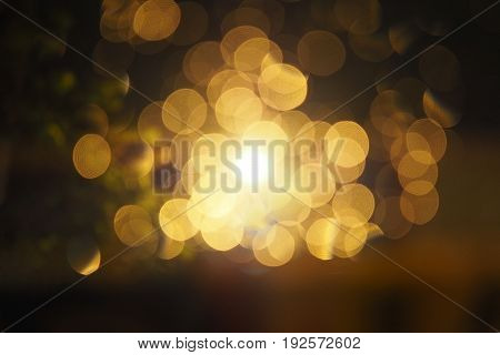 Abstract circular yellow bokeh in dark background gold bubble lights at night. Bokeh Christmas background with circle designs or blurred stars shining glitter magic background