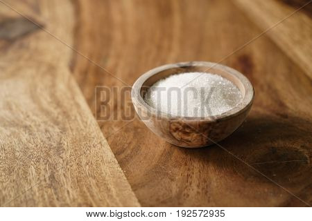 sugar in wood bowl on wooden table, with copy space