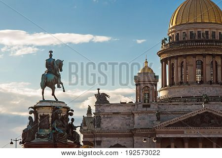 Gold dome orthodox of St. Isaac's Cathedral in Saint-Petersburg and monument to Nikolay the First