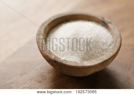 white sugar in wood bowl on wooden table, with copy space