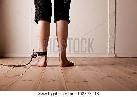 Rear View Of Rope And Shackle Around Ankle