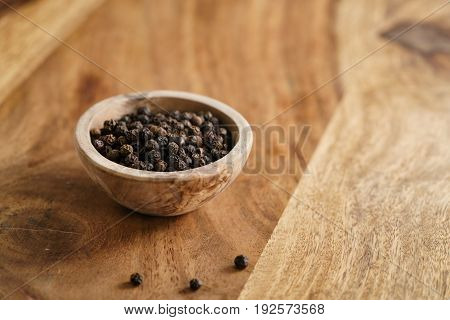 black dry pepper in wooden bowl on table, with copy space