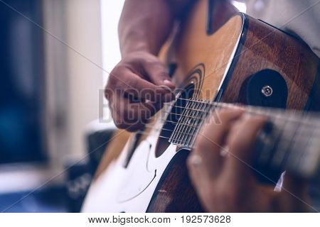 the guy playing the acoustic guitar, closeup, music concept