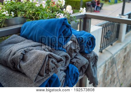 Close up pile of folded blue and grey blankets in outdoors cafe