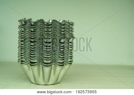 Close up stack of metal cupcake molds on shelf