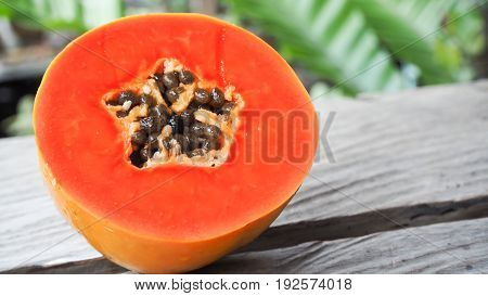 A half of freshly yellow orange papaya on wood table in garden background