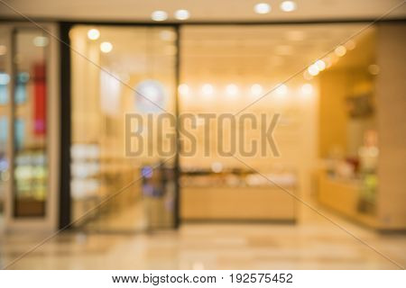 Blurred light or bokeh background of front door bakery shop in shopping mall or department store interior