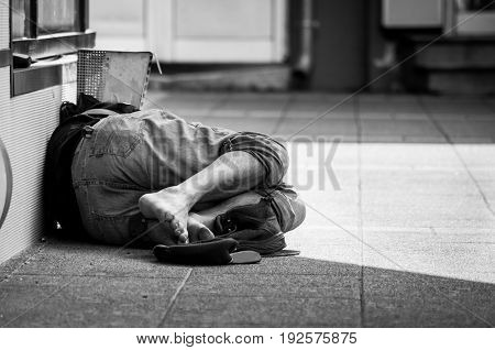 Homeless man sleeps on the street, in the shadow of the building. Street social documentary. Black and white.