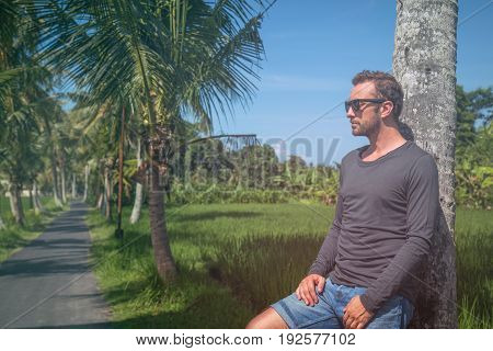 Man standing near empty road with palm trees.