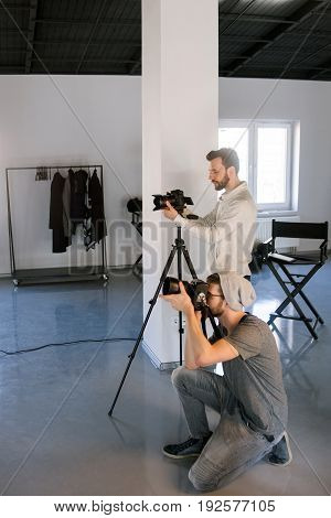 Two photographers taking shots in studio. Professional photo and video production team work together. Fashion photo session backstage