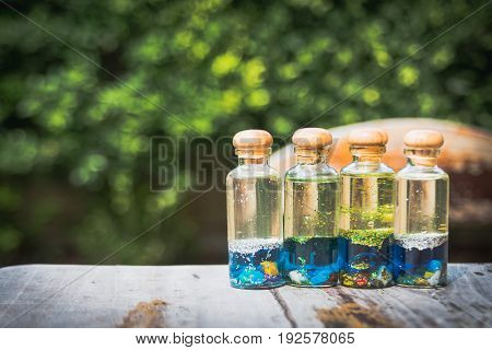 little glass bottles contain oil and blue water filled in diamond dust and tiny stones