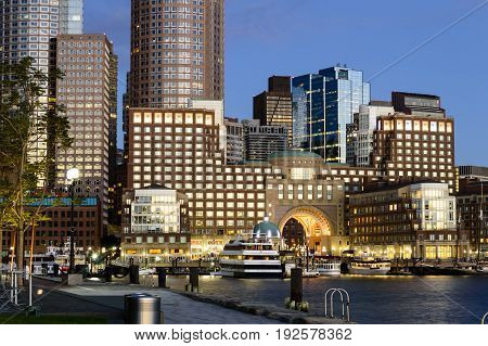 Boston Massachusetts USA - September 15 2016: View from Fan Pier of Rowes Wharf lit by sun rising over Boston harbor