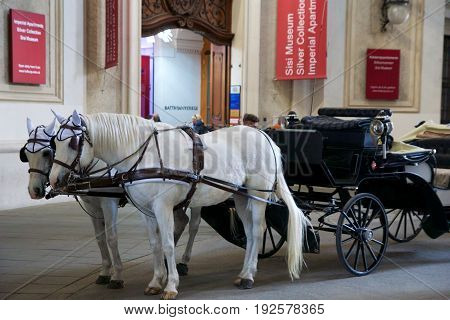 VIENNA, AUSTRIA - APR 29th, 2017: Famous horse-driven carriage at Hofburg Palace in Vienna. It was the Habsburgs' principal winter residence, currently serves as the residence of the President of Austria.