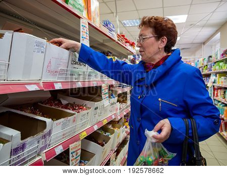 Voronezh, Russia - April 27, 2017: Pensioner buys candy at the supermarket trading network