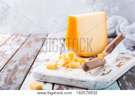 Delicious dutch gouda cheese with cheese cubes and special knife on old wooden table. Copy space.