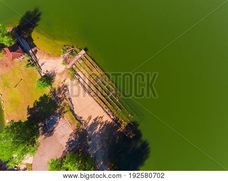 Aerial view, An old destroyed barge that sank sunken by river bank, summer, green water.