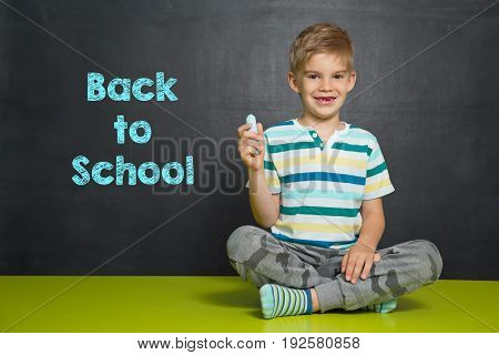 Boy In Front Of School Board With Text Back To School