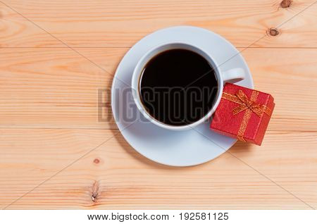 Cup of coffee and gift box on wooden background