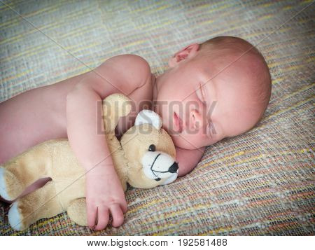 Little baby sleeps with a toy teddy bear