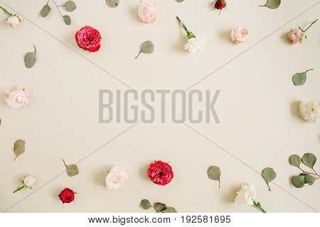 Flowers frame made of beige and red roses eucalyptus leaf on pale pastel beige background. Flat lay top view. Floral wreath frame background.