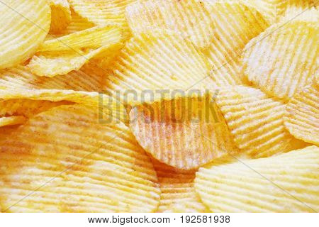 golden closeup wavy potato chips food background selective focus