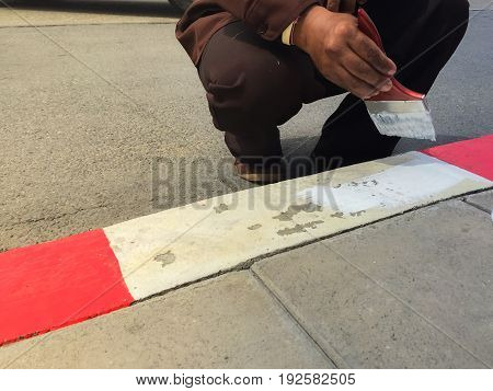 Worker painting White and red line on the curb