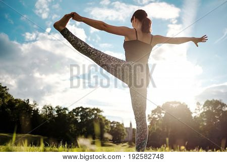 Caucasian woman in yoga standing balance Utthita Hasta Padangusthasana pose, known as extended hand to big toe pose, on meadow in early morning. Back view