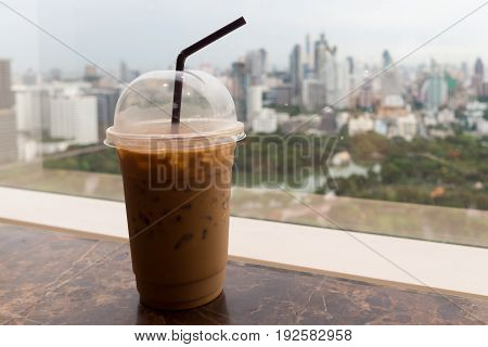 Ice coffee in plastic glass on the table with park and city in background relax before starting hardwork in a day