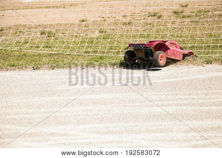 Small radio controlled model car crashed off road. Miniature remote controlled buggy racing hobby