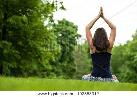 Meditation healthy life exercise concept. Caucasian sporty fit woman doing yoga outdoors. meditating and relaxing in Padmasana Lotus Pose