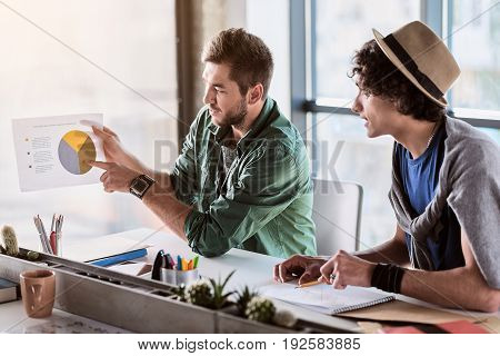 We have great chance. Confident young man is showing graphic to his colleague. They are sitting at table in office