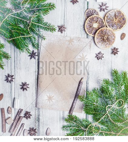 Christmas decoration frame with fir dried oranges pen and paper anise stars pine cones homemade cookies cinnamon sticks. Top view flat lay