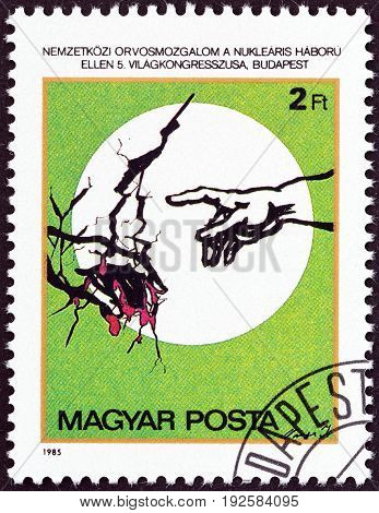 HUNGARY - CIRCA 1985: A stamp printed in Hungary issued for the 5th Congress of International Association of Physicians against Nuclear War, Budapest shows Hand pointing to Cracked Earth, circa 1985.
