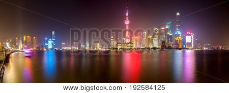 Shanghai, China - Nov 4, 2016: Panorama of Shanghai City skyline by night at The Bund. Features the shoreline and Huangpu River. Long exposure, available-light image. Some low-lying fog moving in.