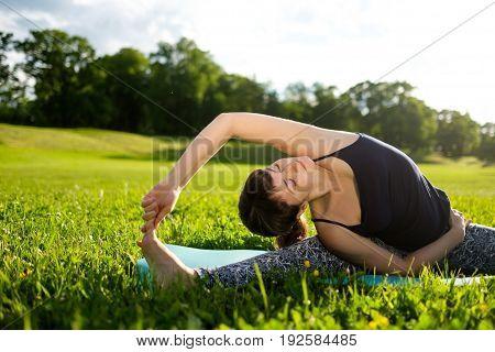 Woman practices balance yoga asana Vrikshasana tree pose in parkoutdoors in the morning.