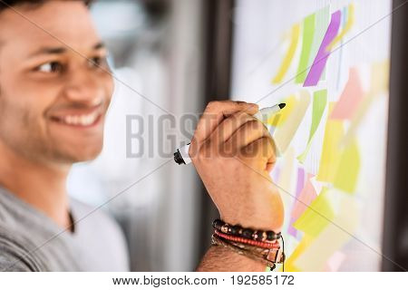 Joyful male freelancer writing his ideas on small colorful papers pasted to glass wall. He is standing and smiling. Focus on marker in his hand