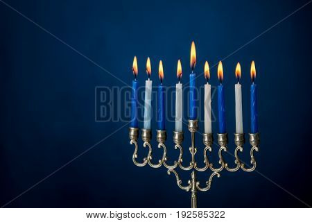 The Hanukkah menorah, traditional candle holder for nine candles for Jewish holiday of Hanukkah on dark blue background