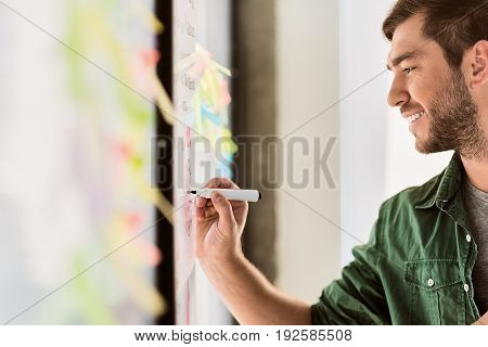 Side view of happy young man drawing graphic on board. He is standing in office and smiling